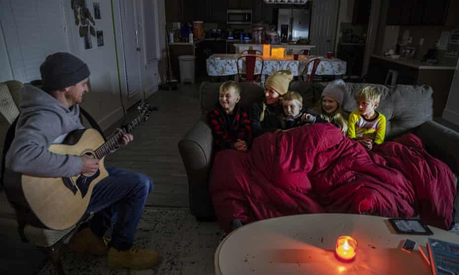 Brett Archibald tries to entertain his family as they attempt to stay warm in their home the BlackHawk neighborhood in Pflugerville, Texas, last week.